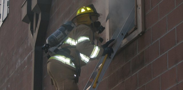 A firefighter climbs up the ladder to rescue a victim Saturday during the Fairmount Township firefighter training.