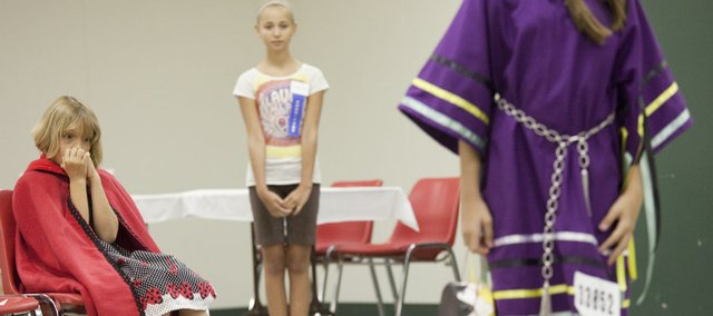 Holly Vesecky, 8, left, a member of the Vinland Valley 4-H Club, waits to compete Monday in the Douglas County 4-H fashion revue. Participants were displaying their sewing projects in the construction category. At center is Hannah Schram, 12, a committee member of the Eudora 4-H Club who was assisting the models, and in the foreground at right is a Choctaw dress modeled by Sabrina Jones,  10, a member of the Clinton Eagles Club. Although there are events throughout the week, the Douglas County Fair really kicks off Friday. Included here is a schedule of events. The Signal will also have a 4-H feature story this week.