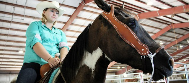 "Gerie Koehler, 15, of Baldwin City waits to show her horse Wyatt Earp at the Open Horse Show at the Douglas County Fair. ""I've been here all weekend,"" Koehler says. ""On Saturday I woke up at 3 a.m. to bathe all the horses for the 8 a.m. show."""