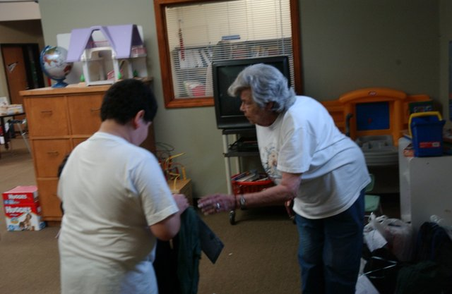 Volunteer Frances Lawhead gives one of the 223 backpacks distributed at the De Soto Multi-Service Center in recent days to 10-year-old Gustavo Marquez. The De Soto Community Church will give away more supplies from 5 to 8 p.m. Friday at Miller Park.