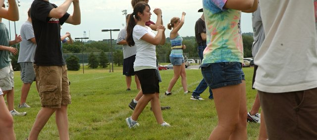 Nelsey Contreras , center in white T-shirt, concentrates as she and other De Soto High School students go through a marching band drill Tuesday at band camp. Contreras is one of about 40 freshmen who will join the award-winning Wildcat marching band for the 2009-2010 year.