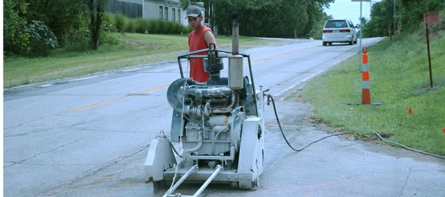 Joe Lowman of Bazin Sawing and Drilling, Louisburg, cuts bad curb and gutter from 83rd Street on Tuesday as the $900,000 resurfacing of the street from Kill Creek Road to the east city limits gets started. Next week, the existing asphalt from Kill Creek to Gardner roads will be removed and work will start to rebuild the road base.