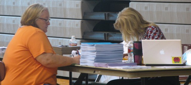 A parent fills out paperwork during all-school enrollment at Basehor-Linwood High School.
