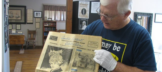 Ken Massingill, Basehor Historical Museum treasurer and historical society board chairman, holds up a 1960s Amelia Earhart commemorative newspaper donated to the museum. The museum opened a new exhibit this month featuring photos and tales from the life of Earhart.
