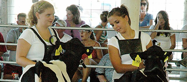 Brittnay George, left, and Kelly Baker of the Vinland Valley 4-H Club show their calves at the dairy show Tuesday evening at the Douglas County Fair in Lawrence.