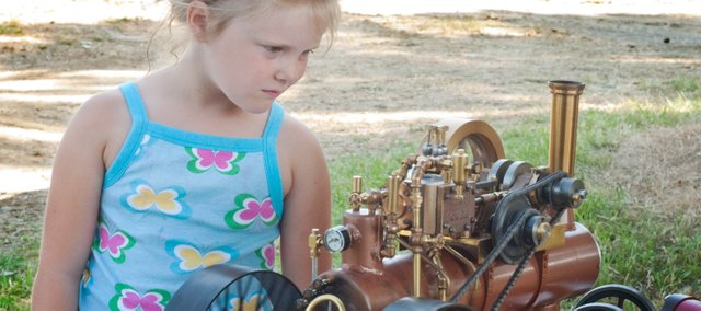 Bobbi Horr, 5, Holton, inspects a scale model steam engine built by Ed Schweder, of St. Joseph, Mo., Saturday at the McLouth Threshing Bee.