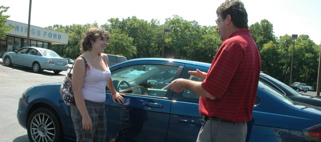 Car shopper Gwenna Davis, of Lansing, takes a look at a Ford Focus with sales and leasing consultant Tom Zukaitis. The car is one of several models available at Bonner Springs Ford for a Cash for Clunkers transaction.