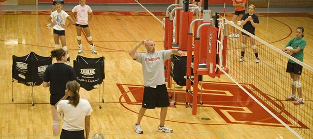 Tonganoxie High volleyball co-coach Brandon Parker demonstrates the form he wants players to use during drills on the first day of practice at THS on Monday afternoon.