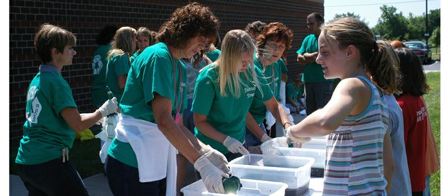 Starside teachers Debbie Neill, Becky Renner, Michelle Aberdeen and Liz Krieger tye-dye shirts during the school's welcome back luncheon. Mackenzie Smith and other girl scouts helped in the preparation of the shirts.