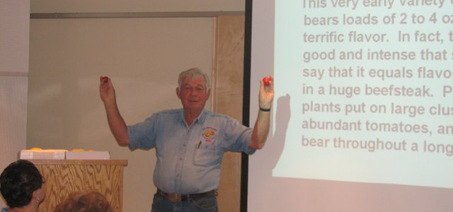 Master gardener Bill Kromer holds up a few of the red heirloom tomatoes he grew in his garden this year.