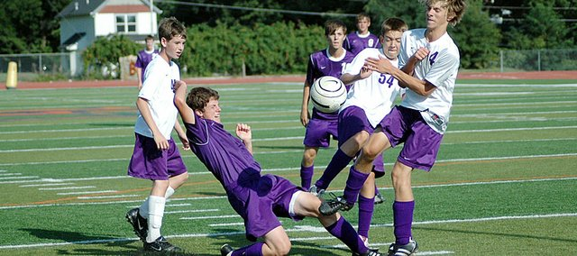 Baldwin High School junior Brandon Baltzell, center, slides into a teammate during a scrimmage Monday afternoon. BHS begins it season at 4:30 p.m. Friday at Tonganoxie.
