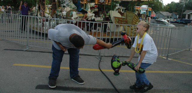 Sixteen-year-old Bobby Hodge, at left, and James Wagner, 12, have a fight with their inflatable prizes at the Tiblow Days carnival Friday, Aug. 28.