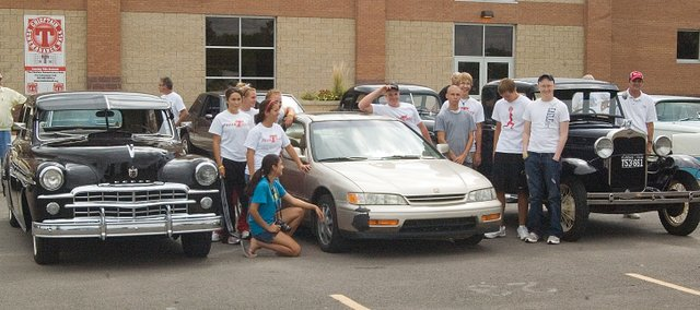 THS students gather around Jeremy Elliott's car at the Team Tongie/Jeremy Elliott Memorial Scholarship Fund Car Show.