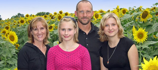 The Grinter family stands in its sunflower field near Tonganoxie. Pictured, from left, are Kris, Callie, Ted and Sidney.