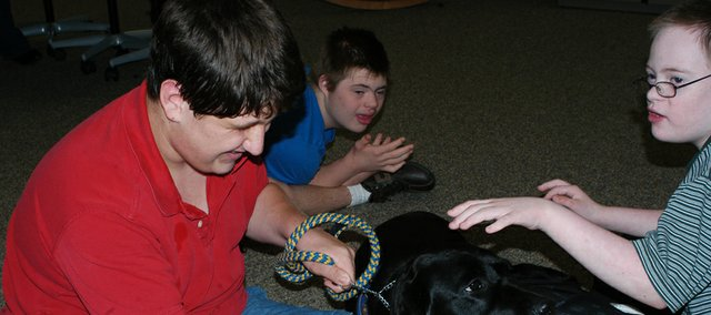 Justin Wagner, right, MCMS eighth-grader, and seventh graders Jesse Bedford, middle, and Matthew Walter pet Fala, during class. Fala, a facility dog, joined MCMS this year and offers friendship and lessons in daily life skills.