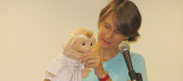 Storyteller Priscilla Howe puts on a show for preschoolers with her baby puppet at the Basehor Community Library. Howe shared stories and sang to the children during the morning program.