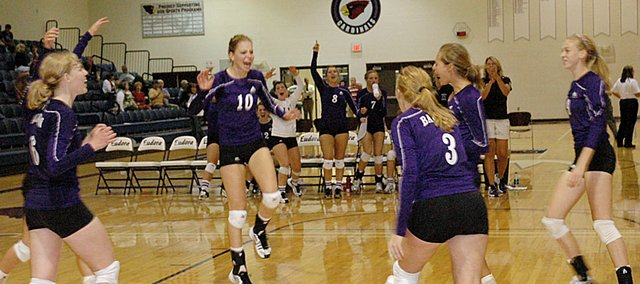 Members of the Baldwin High School volleyball team celebrate after defeating Eudora in straight games Tuesday night. The Bulldogs also beat Bonner Springs, but lost to Basehor-Linwood to begin the season 2-1.