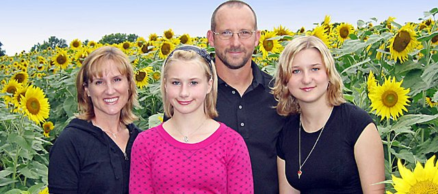 The Grinter family has become famous for a field of sunflowers that have been planted on the family farm between Lawrence and Tonganoxie for the last 30 years. Many people, such as the Grinters, use it for family portraits. From left are Kris, Callie, Ted and Sidney.
