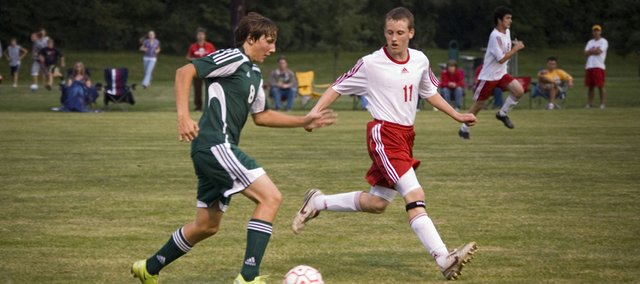 Basehor-Linwood's Patrick Rutherford pushes the ball as Tonganoxie's Matt Briggs closes in on Thursday night at Chieftain Park. The Chieftains won the match, 2-0.
