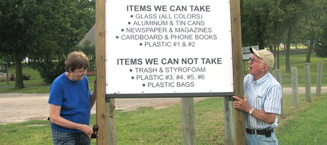 Judy Goens (left) and Chuck Wilderson prop up a monthly recycling sign in Basehor City Park. Basehor's monthly recycling pick up in the park ended in April, which fed the city's creation of a few new recycling options for its residents.
