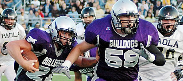 Baldwin High School junior Ryan Rogers, left,  follows junior Jesse Austin (No. 58) during a run during the second quarter of Friday's game against Paola. The Bulldogs were beaten 34-7 by the Panthers to begin the season.