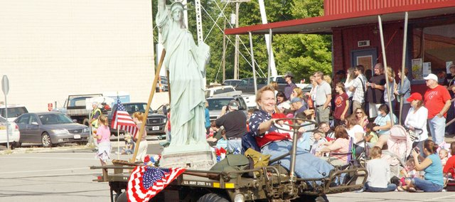 Decked out in red, white and blue, Jenny Booth carried Lady Liberty on the back of her ammunition carrier Saturday at the De Soto Days Parade in downtown De Soto. The parade drew a large crowd, including 9-year-old Julia Eaton (top), who was dressed festively enough to be in the parade.