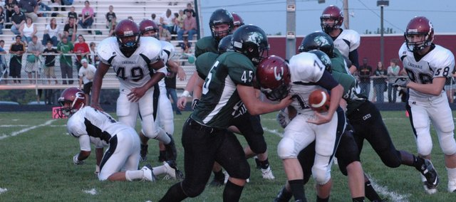 De Soto's Gabe Hamilton (45) and Nick Umholtz wrap up Eudora's Evan Cleveland Friday night at De Soto. The Wildcats fell to the Cardinals, 27-6.