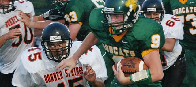 Basehor-Linwood quarterback Brandon Leppke tries to outrun Bonner Springs linebacker Jacob Slattery (45) during the first half Friday. BLHS won the game, 44-21.