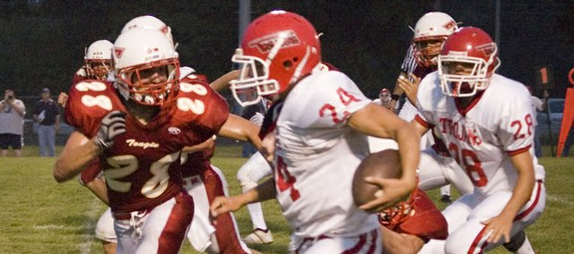 Tonganoxie High defensive back Dylan Scates pursues Osawatomie's Jameson Greenwood during the second quarter of the Trojans' 36-33 victory on Friday at Beatty Field.