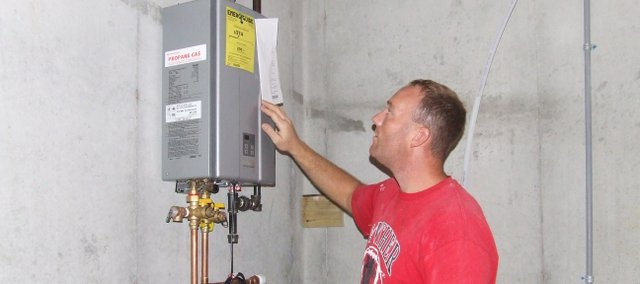 Brian Little, of Bonner Springs, inspects his tankless water heater at the house he is currently building using energy efficient products. In addition to the water heater, Little used structural insulated panels, which provide more insulation than the way a traditional house is built.