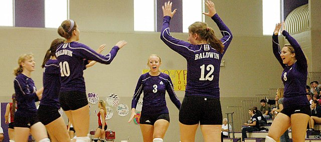 Members of the Baldwin High School varsity volleyball team celebrate winning a point Saturday during their match with Osawatomie. Baldwin lost all four of its matches at its home tournament.