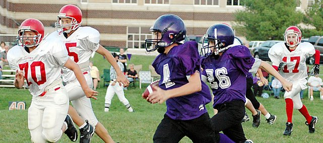 Baldwin Junior High School eighth grader Chad Berg (No. 4) runs around Ottawa defenders during the second half Tuesday. Berg rushed for one touchdown and threw for another as the Bulldogs beat Ottawa 14-8.