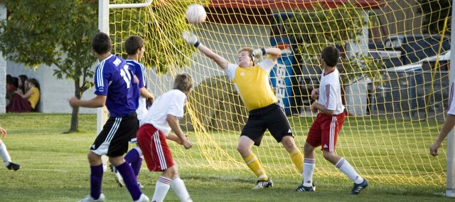 Tonganoxie High goalkeeper Mitch DeHoff knocks away a Piper shot attempt in the first half of the Chieftains' 4-1 victory against Piper on Wednesday.