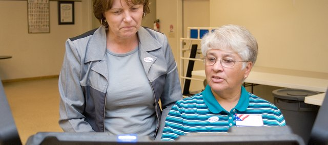 Election worker Dottie Skelley, right, instructs Janine Whitmill on the proper way to use a voting machine during Tuesday's election.