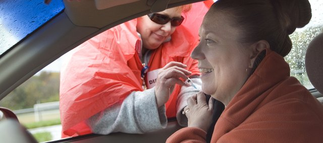 Deborah Whitney, of St. John's Hospital, gives Cathy Adams, Leavenworth, a flu vaccination during an October 2008 drive-thru flu shot clinic in Leavenworth. Leavenworth County Health Department coordinator Karen Savage talks about the importance of the flu vaccination.