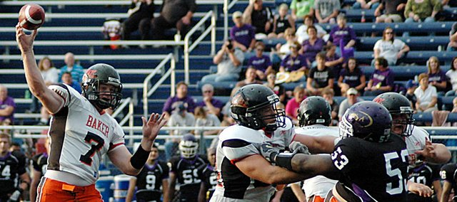 Baker University senior Mack Brown, center, stands in the pocket as he throws a pass downfield during the second quarter Saturday at Avila. Brown threw for 180 yards and three touchdowns as the Wildcats routed the Eagles 41-0. It was Baker's first win of the 2009 season.