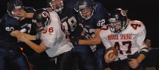 With his brother, Jake Barren (56), clearing the way, Bonner Springs running back Max Barren (47) turns the corner on a run during the Braves' loss to Mill Valley.