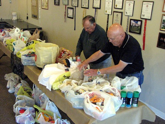 Basehor Veterans of Foreign Wars members Phil Jenkins and Hank Nahrebeski look through some of the items donated to the VFW. The VFW organized a drive at the beginning of September to receive goods to be sent to military members in Iraq and Afghanistan.
