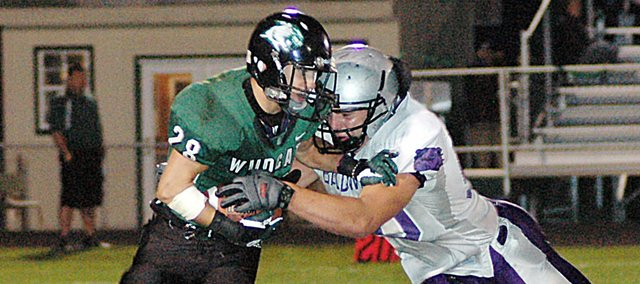 Baldwin High School junior Landon Ausherman, right, tackles De Soto senior Dylan Burford in the backfield Friday night. The Wildcats beat the Bulldogs 14-7.
