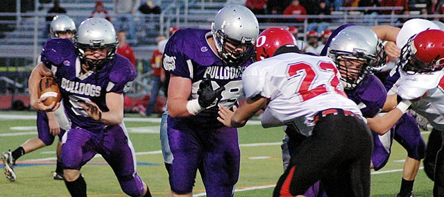 Baldwin High School junior Josh Hoffman, left, follows his blockers during a first quarter run. Hoffman scored Baldwin's only touchdown, as he rushed in from 12 yards out. Baldwin lost to Ottawa 18-7.