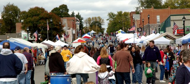 Crowds walk Saturday amongst the various vendors on Main Street at EudoraFest.