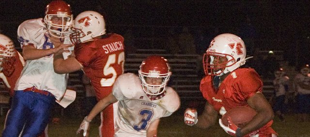 Austen Holloway breaks left, around the block of guard Nathan Stauch, on his way to a 40-yard touchdown run that opened the floodgate for Tonganoxie High in a 75-12 walloping of Santa Fe Trail on Friday night at Beatty Field.