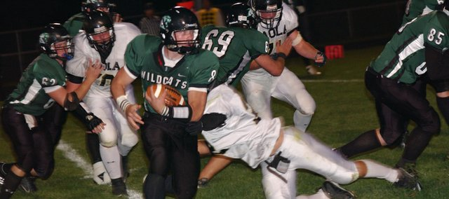 De Soto quarterback Logan Clark runs for a key first down deep in Paola territory as Lyle Logan (69) and Joseph Seidl (62) block in the Wildcats' homecoming game Friday. The Wildcats scored their lone touchdown of the game on the drive but lost the game 7-6.