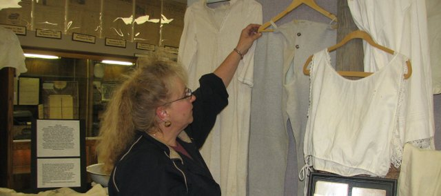 "Basehor Historical Museum Director Carla Crawford feels the fabric of a pair of men's long underwear from the early 1900s. The museum opened the exhibit, ""Victor and Victoria' Secret,"" Oct. 1 as a sequel to its previous display, ""Victorian Secret,"" that depicted the history of women's undergarments."
