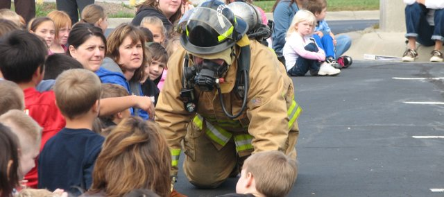 Fairmount Township Cadet Jake Bennett crawls past Basehor Elementary students Monday to demonstrate how firefighters move through a burning building. The fire department visited Basehor-Linwood schools to talk about fire safety.