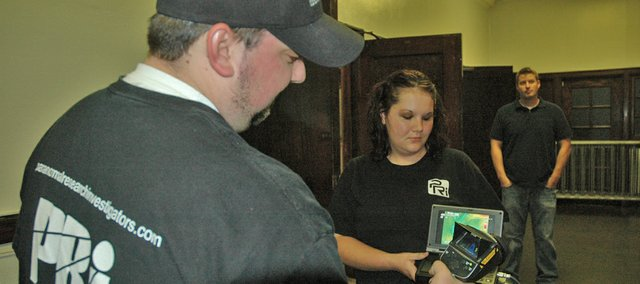Paranormal investigator Nick Spantgos, at left, demonstrates how his thermal- imaging camera works. Spantgos attended the media night at Memorial Hall to do more investigations of possible paranormal activity he had recorded during a previous visit.