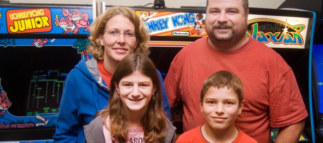 Heather and Doug Shoemaker, back row, and their children Harlan, 12, left, and Gunner 10, stand in front of a few classic arcades at the recently opened Doug'z Arcade.