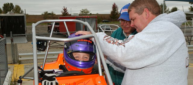 As Steve Chick Sr. watches, Steve Chick Jr., right, straps his 7-year-old daughter Amanda into her quarter midget race car before she took it out for practice laps Saturday at the Topeka Kansas Quarter Midget Association track in Topeka.