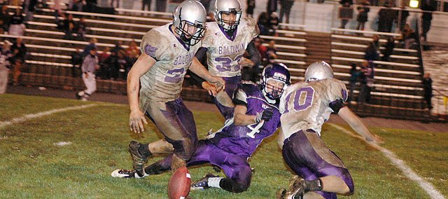 A trio of Baldwin High School defensive players break up a Louisburg pass Friday night. Pictured from left are junior Ryan Rogers, sophomore Jake Mindez and junior Will Von Bargen.
