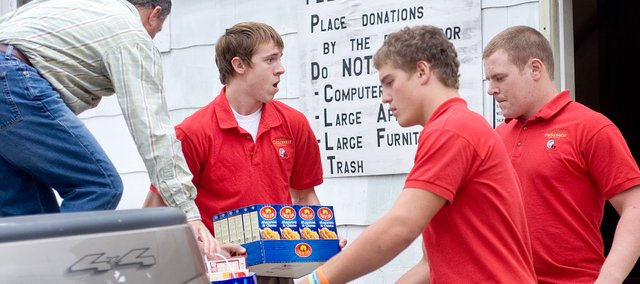 Tonganoxie High School football coach Mark Elston, left, gathers food for THS seniors Dane Gonser, Jeremie Maus and Dylan Young to carry into the Good Shepherd Thrift Store and Food Bank. Elston said the nearly 700 items of food collected by the football team on Tuesday was just a way to give back to the community.